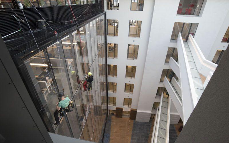 Nettoyage sur corde de vitres à l'intérieur d'un bâtiment